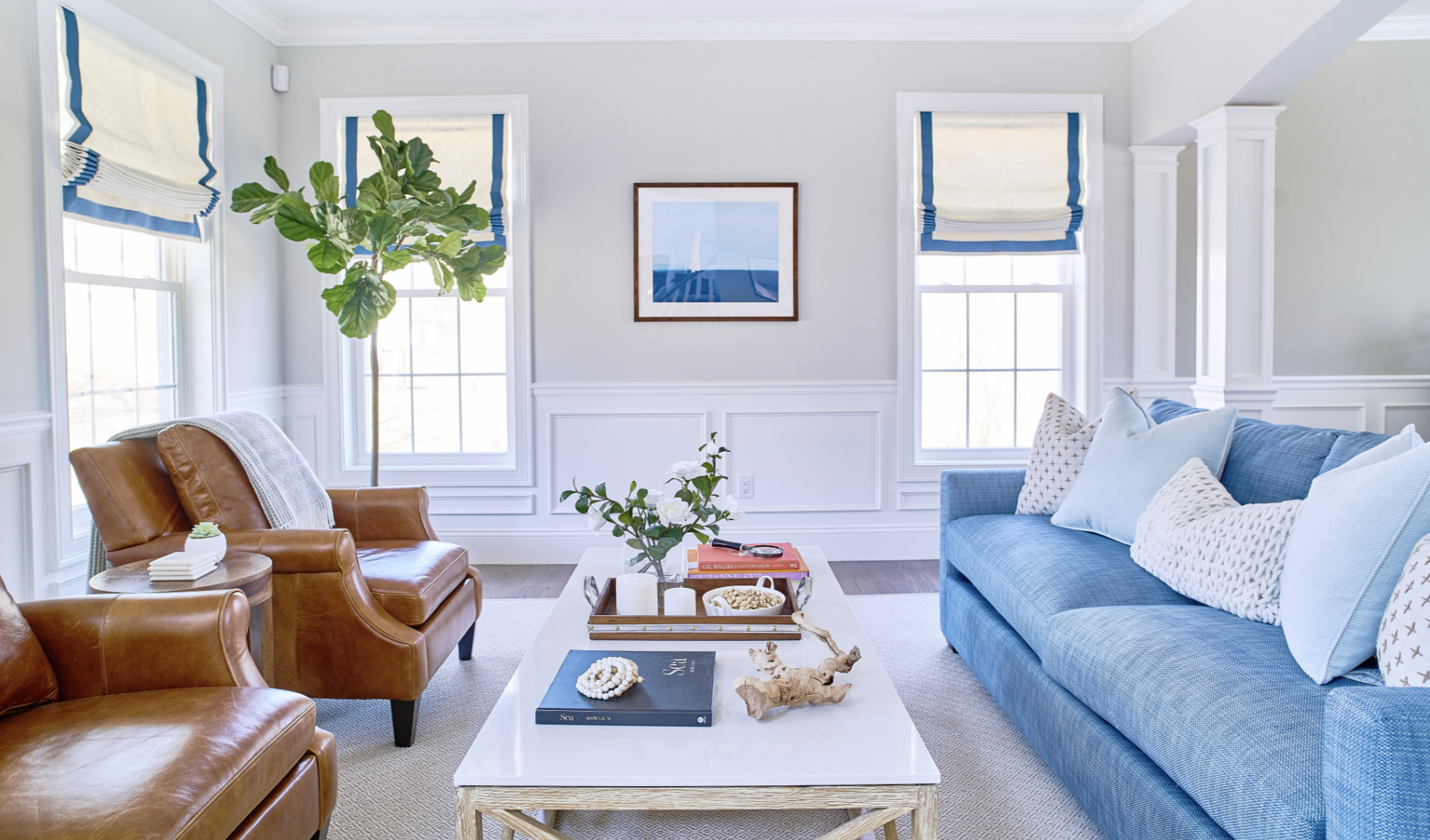 warm cool living room leather chairs blue sofa white walls wainscoting fiddle leaf interior design blakely RI