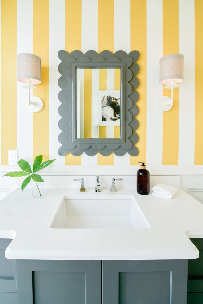wallpaper powder room yellow daffodil stripes gray framed mirror greenery white vanity sconces