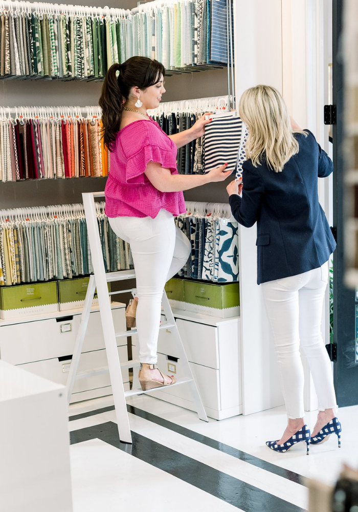 blakely interior design kingstown ri a day in the life designer two designers looking at fabric swatches standing on ladder